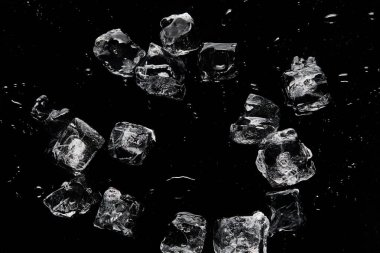 top view of melting transparent refreshing ice cubes isolated on black