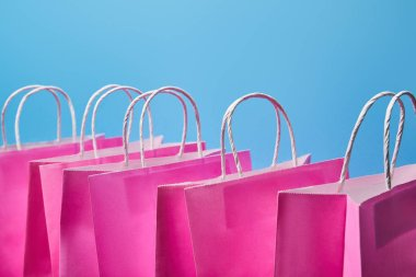Few pink paper shopping bags on blue background stock vector