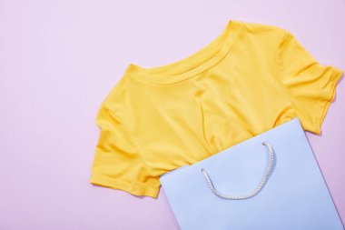 top view of yellow t-shirt in purple shopping bag on violet
