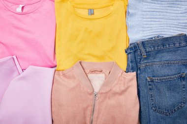 flat lay with colorful t-shirts, jeans, hat and jacket