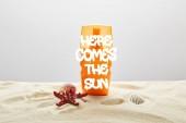 sluneční clona v oranžovém lahvích na písku s hvězdice na šedém pozadí se sem blíží slunce