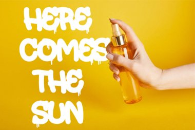 cropped view of woman holding bottle with sunscreen spray on yellow background with here comes the sun lettering