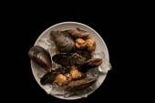 Draufsicht auf gefrorene rohe Herzmuscheln und Miesmuscheln mit Eiswürfeln auf weißem Teller isoliert auf schwarzem Teller