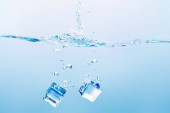 transparent pure water with splash and square ice cubes on blue background