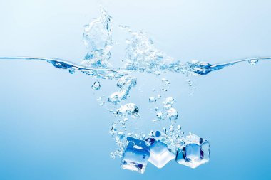 Pure water with splash, bubbles and ice cubes on blue background stock vector