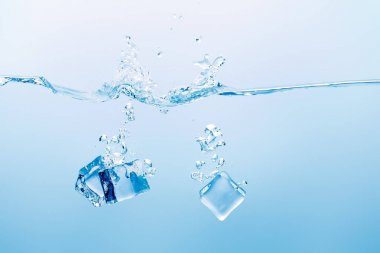 transparent pure water with splash and ice cubes on blue background