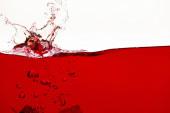 liquido rosso luminoso con spruzzi e bolle isolate sul bianco
