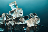 stack of transparent melting ice cubes on emerald background