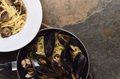 top view of delicious pasta with mollusks and mussels on wooden cutting board on weathered grey background