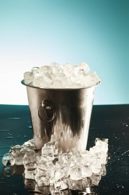 transparent ice cubes in metal bucket with water drops on surface on emerald and white background