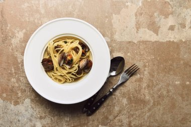 top view of delicious pasta with mollusks served with spoon and knife on weathered beige background