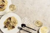 pohled na delikátní těstoviny s plody moře podávané s bílým vínem a strouhané sýry na šedém povrchu s prostorem pro kopírování