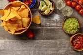top view of Mexican nachos served with guacamole and salsa on weathered wooden table