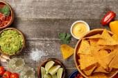 pohled na Mexické nachos podávané se sýrovou omáčkou, guacamolem a salsou na ošlehané dřevěné stolce