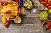 top view of Mexican nachos served with guacamole, cheese sauce and salsa on weathered wooden table