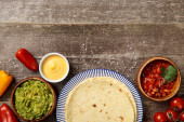 top view of Mexican tortilla with guacamole, cheese sauce and salsa on weathered wooden table