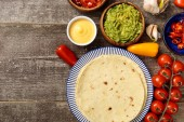 top view of Mexican tortilla with guacamole, cheese sauce and salsa on weathered wooden table with copy space