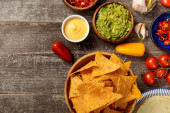 top view of Mexican nachos served with guacamole, cheese sauce and salsa on wooden table