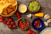 top view of Mexican nachos served with guacamole, cheese sauce and salsa on wooden rustic table