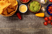 top view of Mexican nachos served with guacamole, cheese sauce and salsa on wooden table with salt