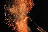 cosmetic brush with colorful orange powder explosion on black background