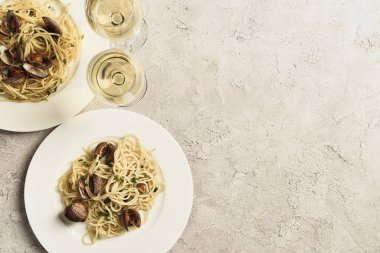 top view of delicious pasta with seafood served with white wine in glasses on textured grey surface with copy space