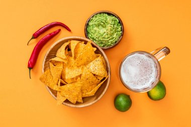Top view of crispy nachos, guacamole, beer, limes and chili peppers on orange background, Mexican cuisine stock vector