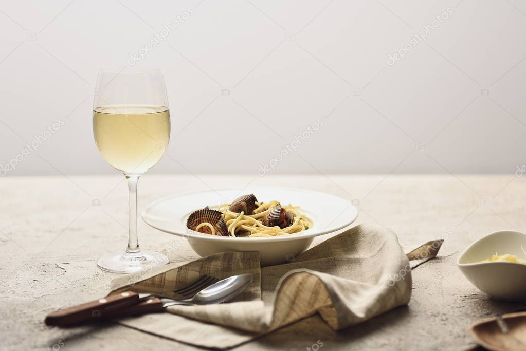 Italian pasta with seafood served with white wine, napkin and cutlery isolated on grey stock vector