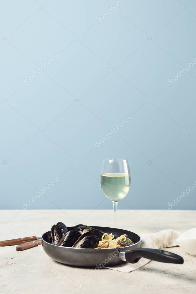 Delicious Italian pasta with seafood served in frying pan with white wine isolated on blue stock vector