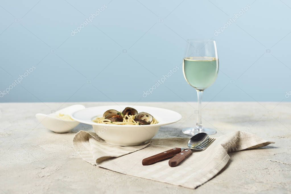 Delicious Italian spaghetti with seafood served with grated cheese and white wine on napkin near cutlery isolated on blue stock vector