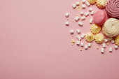 Felülnézet a rózsaszín édes macaroons, sárga habcsók és mályvacukrot a rózsaszín háttér