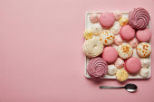 Photo Flat lay with assorted meringues and macaroons on square dish with spoon on pink background
