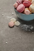 Photo Blue bowl with pink macaroons, soft zephyr and small pink and white meringues with sugar pieces on gray background