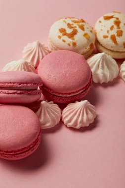 Tasty french macaroons with meringues on pink background