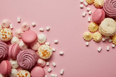 Smashed delicious sweet meringues, macaroons and small marshmallows pieces on pink background stock vector