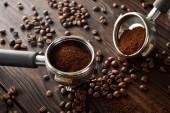 Portafiltry s aromatickou čerstvou kávou na tmavém dřevěném povrchu s kávovými fazolemi