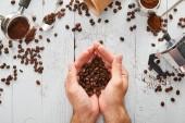 Pohled na mužskou ruku s kávovými fazolemi pod bílou dřevěnou plochou se lžíci, papírovým šálkem, portafiltračním a geyserským kávovar