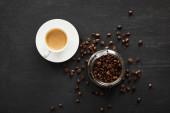 Vista dallalto della tazza bianca di caffè sul piattino vicino al vaso di vetro con chicchi di caffè
