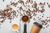 Horní pohled na papírový šálek mezi okénkem a šálek kávy espreso na bílém dřevěném povrchu s kávovými fazolemi
