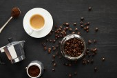 Top view of glass jar with coffee beans near geyser coffee maker, cup of coffee and spoon on dark wooden surface with coffee beans