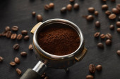 Fotografie Portafilter filled with fresh coffee on dark wooden surface with coffee beans