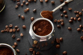 Fotografie Part of geyser coffee maker with ground coffee near spoon on dark wooden surface with coffee beans