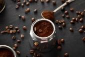 Část gejzíru kávy se mleté kávou blízko lžíce na tmavém dřevěném povrchu s kávovými fazolemi