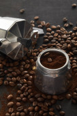 Geyser coffee maker on dark brown wooden surface with coffee beans