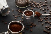 Parts of geyser coffee maker near spoon with coffee and portafilter on dark wooden surface with coffee beans