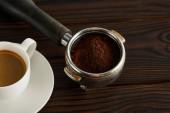 Portafilter with fresh ground coffee near cup of espresso on dark wooden surface
