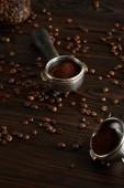Portafilters őrölt kávéval a sötét fa felületen kávébabbal