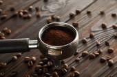 Portafilter riempito con caffè macinato fresco su superficie di legno scuro con chicchi di caffè