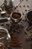 Portafilter közelében kanál, gejzír kávéfőző és üvegedénybe a kávé bab sötét fából készült felület