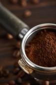Portafilter riempito con caffè macinato fresco sotto superficie scura con chicchi di caffè